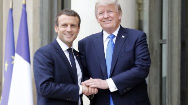 A different handshake:  French President Emmanuel Macron welcomes US President Donald Trump at the Elysee Presidential Palace on July 13.
