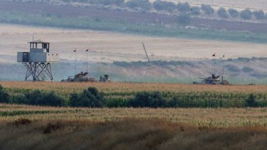 Clashing with IS ... Turkish army tanks hold positions near the border with Syria, in the outskirts of the village of Elbeyi, east of the town of Kilis, in southeastern Turkey.