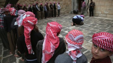 Yazidi boys line up to pray at their religion's holiest temple last week in the Nineveh Province village of Lalish, Iraq.