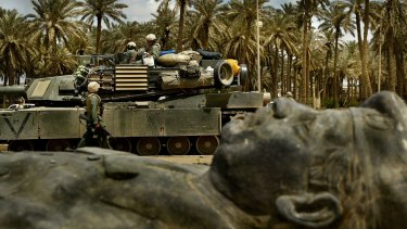 A US tank unit passes one of the many fallen statues of former Iraqi dictator Saddam Hussein on the streets of Baghdad in March 2003.