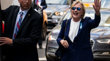Democratic presidential candidate Hillary Clinton waves as she walks from her daughter's apartment building on September 11, 2016, in New York, two hours after the incident.