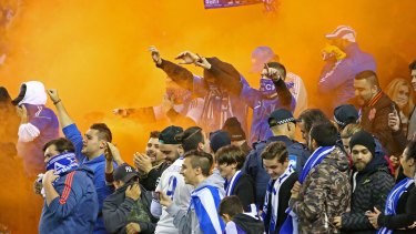 A flare is set off among Greek supporters in the crowd.