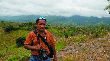 Killing fields: Journalist Aquiles Zonio, who withdrew from the doomed convoy on the morning of the Ampatuan massacre, pictured here at the killing site.