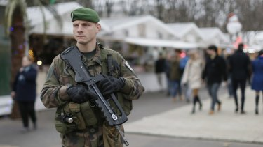 A French soldier patrols the Christmas market along Champs Elysees in Paris.