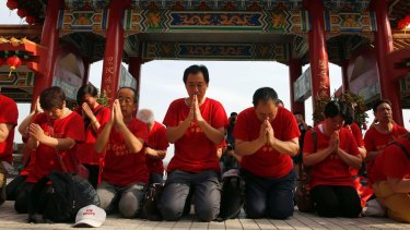 Chinese relatives of passengers aboard missing Malaysia Airlines flight MH370 pray at the Thean Hou temple in Kuala Lumpur