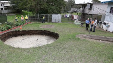 Council workers inspect the massive hole.