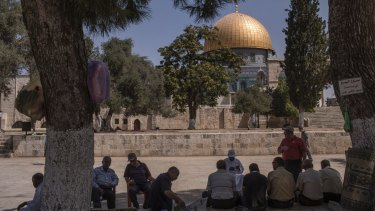 Locals sit near the Dome of the Rock in the Israeli-occupied Old City of Jerusalem.