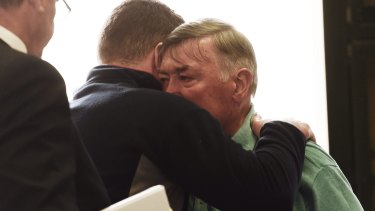 Barry Lyttle hugs his father Oliver outside Central Local Court.