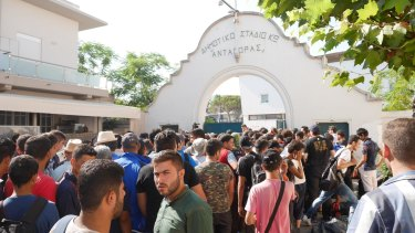 Syrian migrants wait to enter a stadium in Kos to register as refugees.
