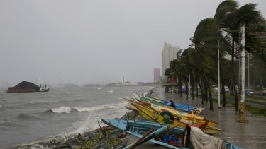 Small fishing boats are placed by the seawall as strong winds and rain brought by Typhoon Koppu hit Manila.