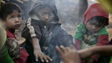A family who fled violence in Salipara village in Myanmar sit at a Rohingya refugee camp in Bangladesh.
