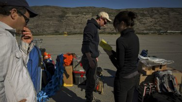 Laurence Smith, head of the geography department at the University of California, Los Angeles, left, and Vena Chu, right, add up the weight of baggage researchers plan to take out for fieldwork before leaving from Kangerlussuaq in July.