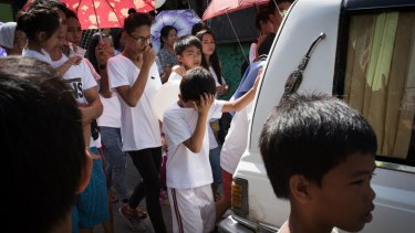 Children and relatives mourn while walking behind a hearse during a funeral held for Alex Hongco killed in a police drugs raid in December.