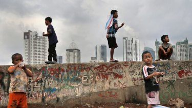 Children play against the Jakarta skyline.