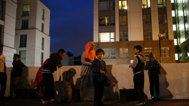 Children stand outside as they are evacuated with their families from the Chalcots Estate, in Camden, north London.