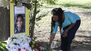 Jeanette Williams places a bouquet of roses at a memorial for Sandra Bland near Prairie View A&M University in Texas on Tuesday.