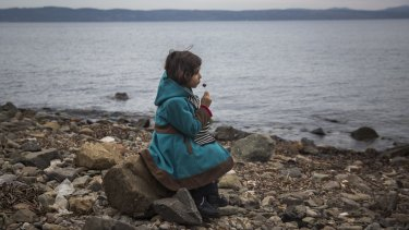 A Syrian girl eats a lollipop after her arrival on a small boat from the Turkish coast on the Greek island of Lesbos on Monday. The US had committed to increasing its Syrian refugee intake this year until the Paris attacks made politicians reconsider the plan.