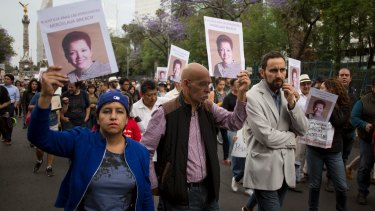 People hold up photos of Mexican journalist Miroslava Breach during a march in Mexico City.