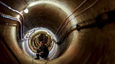 Electrician Glenn Kelly works in the 1890s ventilation tunnel under Victoria's Parliament House.