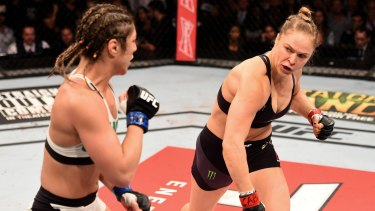 Ragin' cagin': Ronda Rousey (right) of the United States throws a punch at Bethe Correia of Brazil in their UFC women's bantamweight championship bout during the UFC 190 event in Rio de Janeiro.