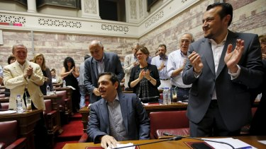 Greek Prime Minister Alexis Tsipras (seated) is applauded by his colleagues in the ruling Syriza party inside the Greek parliament.
