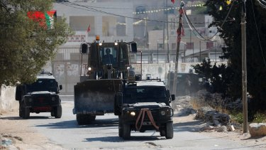 Israeli security forces and a military bulldozer raid the occupied West Bank village of Deir Abu Mashal near Ramallah on Saturday after the Jerusalem attack.
