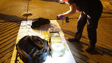 Officers examine drugs seized from a dinghy as it moored in Parsley Bay on the NSW Central Coast.