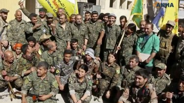 Fighters from the US-backed Syrian Democratic Forces (SDF) celebrating their victory in Raqqa, Syria.