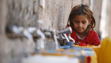 A girl fills a container with water from a public tap amid an acute shortage of water, in the old city of Sanaa, Yemen, on Wednesday.