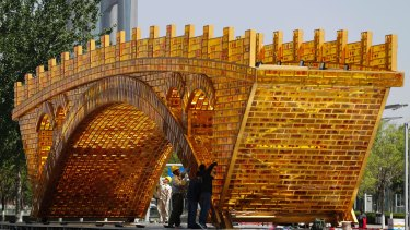 Workers install wires on a 'Golden Bridge of Silk Road' structure on a platform outside the National Convention Centre in Beijing.