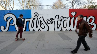 "A boy skates by a painted wall reading ""Paris, I love you"", in Paris last week."