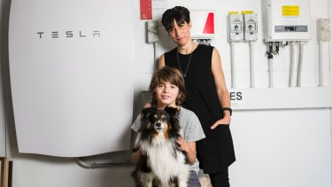 Canberrans have a better attitude to large scale renewable energy than most Australians do. Sophie Jensen with her son Huxley 12, and dog Ghillie, in front of their tesla battery, solar inverter and interface system.
