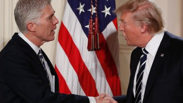 President Donald Trump shakes hands with Judge Neil Gorsuch on Tuesday.