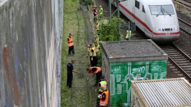 Police officers lay barbed wire on the edge of train tracks near the Convention Centre in Hamburg in preparation for the upcoming G20 Summit.