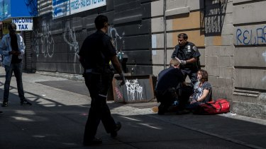 A woman is treated by emergency medical workers during the mass overdose in Brooklyn in July.
