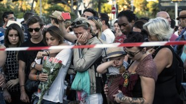 People react as they gather at a makeshift memorial near the scene of the carnage in Nice.