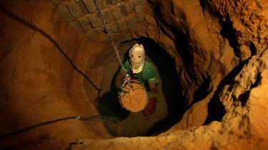 A Palestinian tunnel digger, wearing a mask to conceal his identity, removes sand in a bucket from a tunnel underground in Rafah, in the southern Gaza, in 2007.
