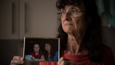 Maureen McIlquham holds a photo of herself and her daughter, Michelle, who died of meningitis in 2009.