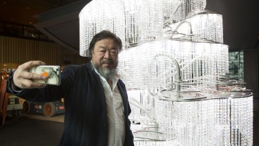 Ai Weiwei takes a selfie at the National Gallery of Victoria in front of his work Chandelier with Restored Han Dynasty Lamps for the Emperor, 2015, part of the exhibition Andy Warhol|Ai Weiwei.