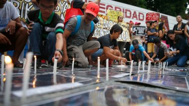 Protesters light candles on photos of alleged victims of extra-judicial killings during a rally outside the Philippine National Police headquarters on Wednesday.