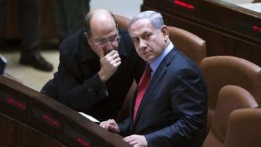 Israeli Prime Minister Benjamin Netanyahu listens to party colleague and Defence Minister Moshe Yaalon during a session of Israel's parliament on Monday.