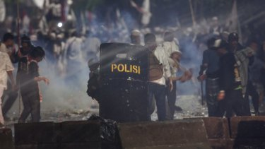 Police fire tear gas on protesters in Jakarta last month.