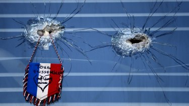 A French flag hangs from broken glass from a bullet hole in the window of the restaurant on Rue de Charonne, Paris, where attacks took place on Friday.
