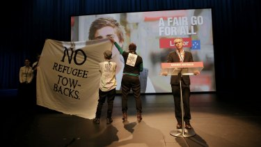 Protesters disrupt the debate on Labor's asylum seeker policies.