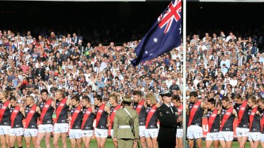 Special occasion: The Australian flag is taken to half-mast before the Essendon-Collingwood match at the MCG.