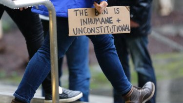 """A person walks away from the federal courthouse in Seattle carrying a sign that reads """"The Ban is Inhumane and Unconstitutional"""" on Friday."""