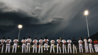 Canberra Cavalry players line up during a moment of respite from the supercell storm in Canberra on Saturday.