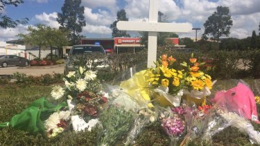 Flowers laid outside Hungry Jack's in Hoxton Park, where Courtney Topic was shot dead.