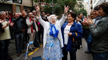 An elderly lady is applauded as she celebrates after voting at a school assigned to be a polling station by the Catalan government in the Gracia neighbourhood of Barcelona.
