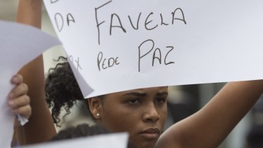 "A woman holds a sign that reads in Portuguese ""Favela asks for peace"" during the burial of Roseli Jesus on Tuesday."